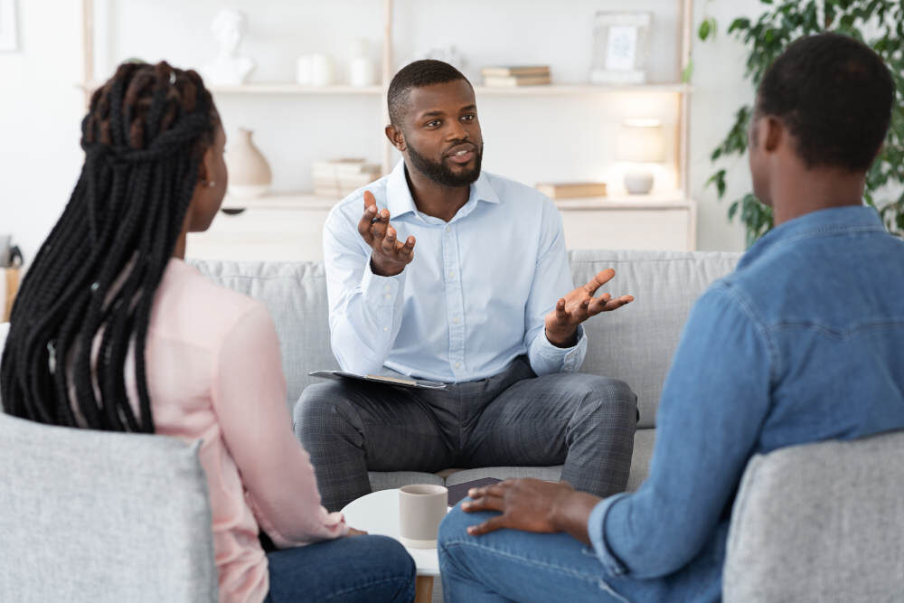 Family Psychotherapy. African American Couple Listening To Counselor's Advices During Therapy Session
