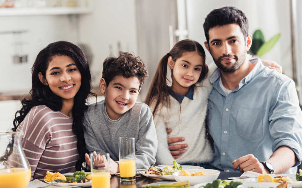 cheerful latin family hugging and looking at camera during lunch at home